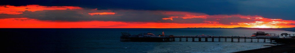 Sunset over the sea showing Brighton and The West pier (PRINT) by unkown
